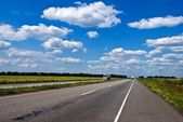 Asphalt road under a clouds — Stock Photo