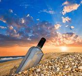Bottle on a sea coast at the sunset — Stock Photo