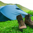 Tourictic boots near a tent on a grass - Stock Photo