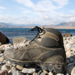 Tourist boot on a seashore - Stock Photo
