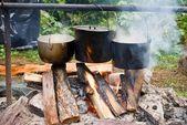 Three touristic caldron in a campfire — Stock Photo