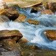 Small blue river flow by a stones — Stock Photo