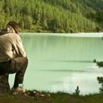 hombre sentado cerca del lago — Foto de Stock