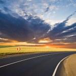 Asphalt road turn at the sunset — Stock Photo