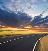 Asphalt road turn at the sunset — Foto Stock