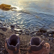 Touristic boots on a sea coast at the early morning - Stock Photo