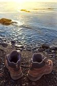 Touristic boots on a sea coast at the early morning — Stock Photo
