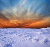 Sunset in a snowbound plain — Stock Photo