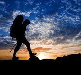 Silueta caminante sobre un fondo de atardecer — Foto de Stock