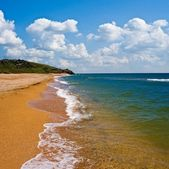 Sandy sea coast by a summer day — Stock Photo