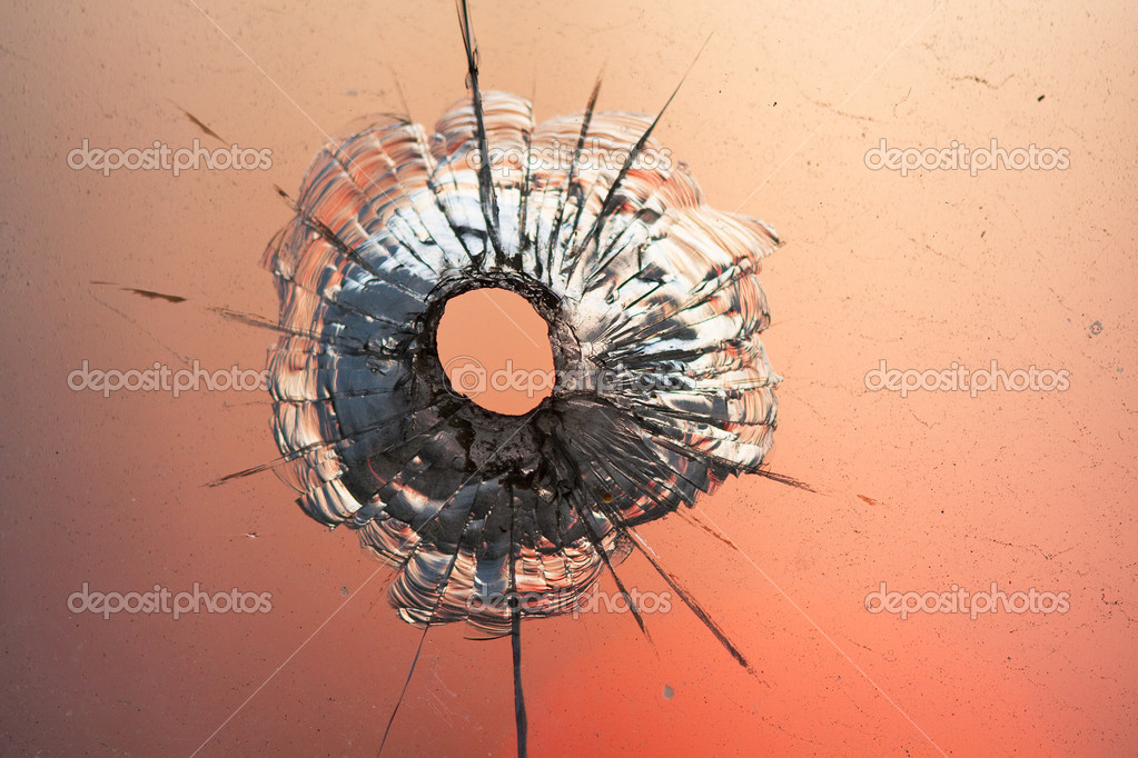 Bullet hole in window on the background sunset sky — Stock Photo #8320705