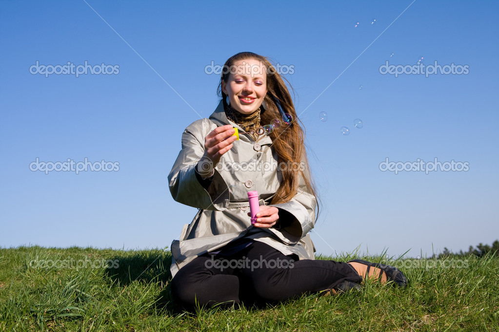 Beautiful girl makes soap bubble on a grass — Stock Photo #8412805