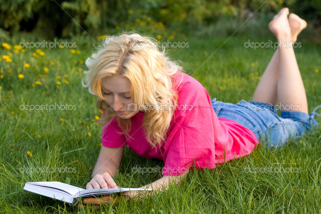 Girl reads the book on a grass — Stock Photo #8412848