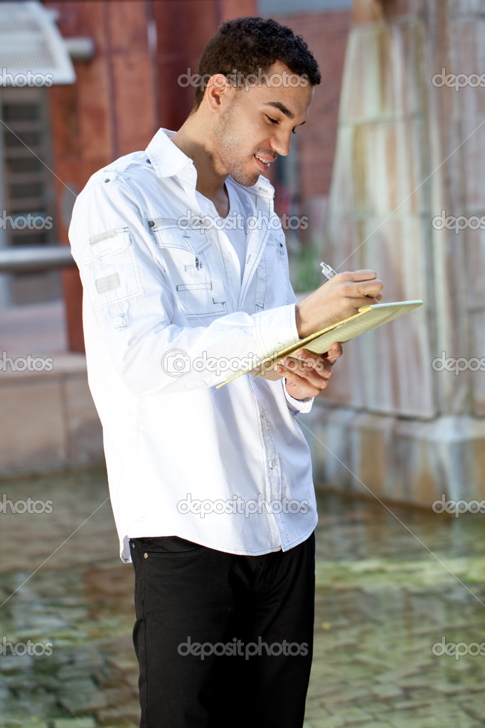 Good Looking Guy writting on a note pad — Stock Photo #10373038