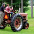 Stock Photo: Grandfather and Grandson Driving a Vintage Tractor