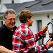 Grandfather and Grandson driving a tractor - Stock Photo