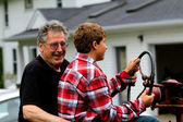 Grandfather and Grandson driving a tractor — Stock Photo