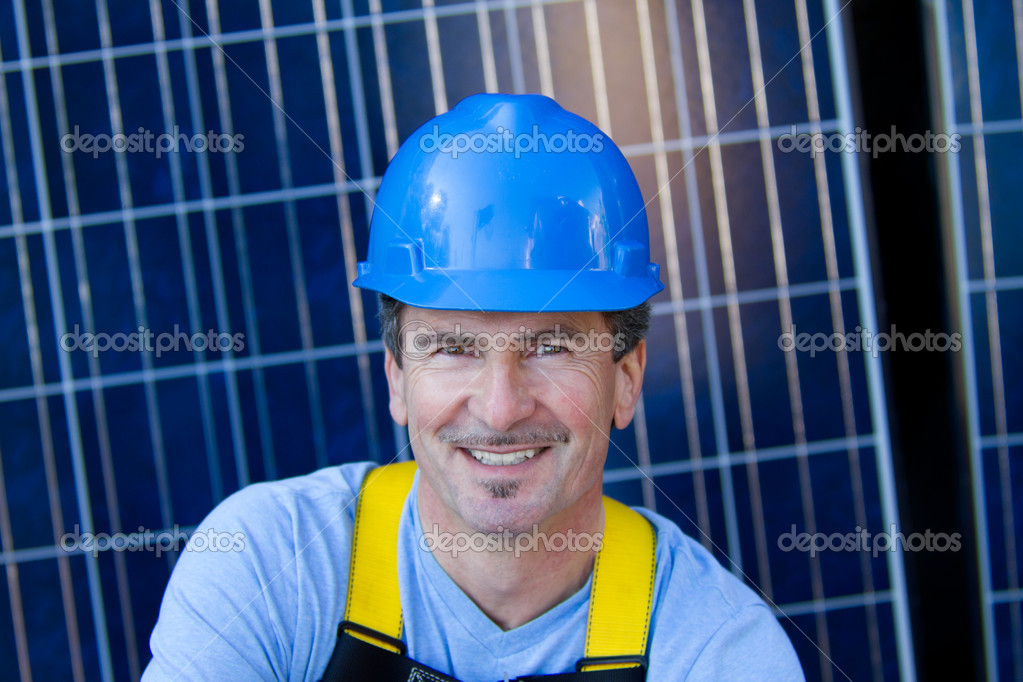 Close up of a Man in his forties overseeing a Solar Instalation with Solar Panels behind him — Stock Photo #8791864