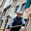 Gondolier navigates on the channel of Venice - Stock Photo