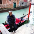 Gondolier welcoming tourist on a canal in Venice — Stock Photo