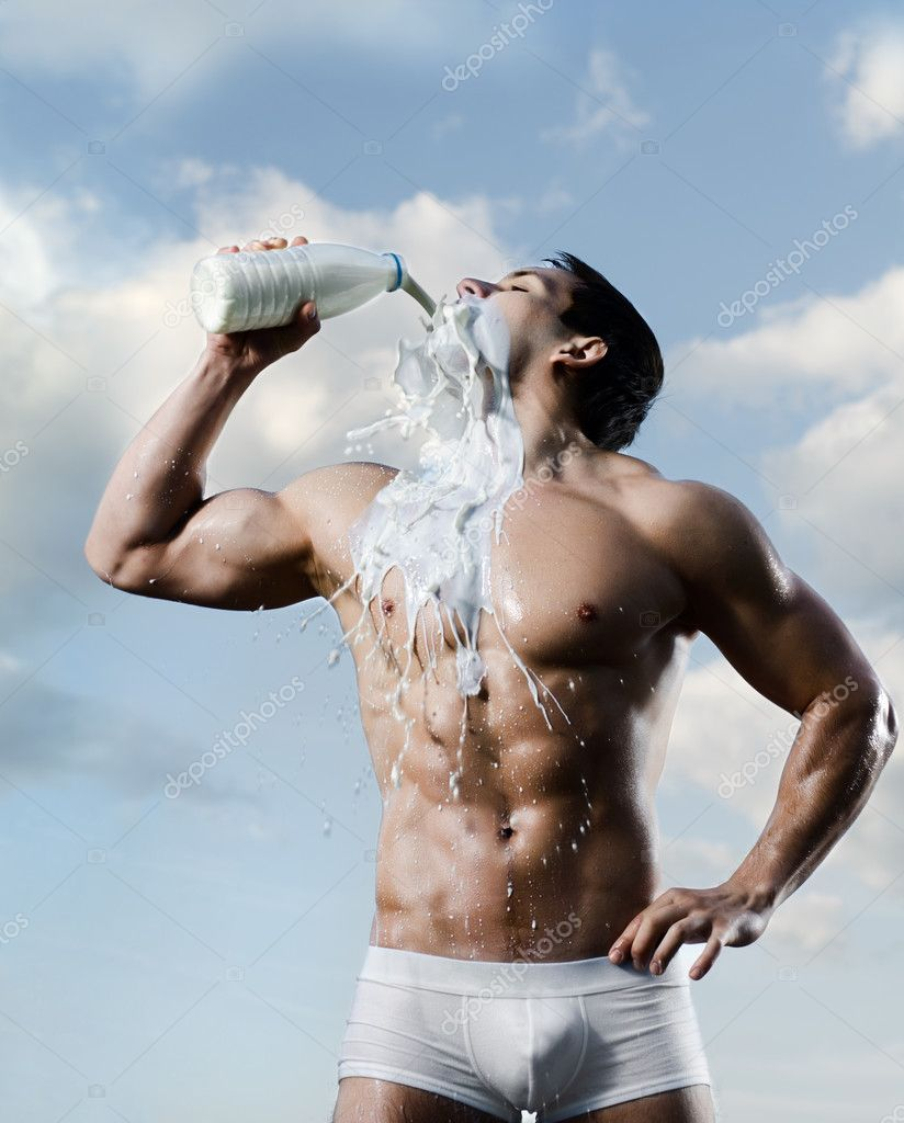 The very muscular handsome sexy guy on sky background, drink milk — Stock Photo #8205207