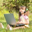Little girl with computer - Stock Photo