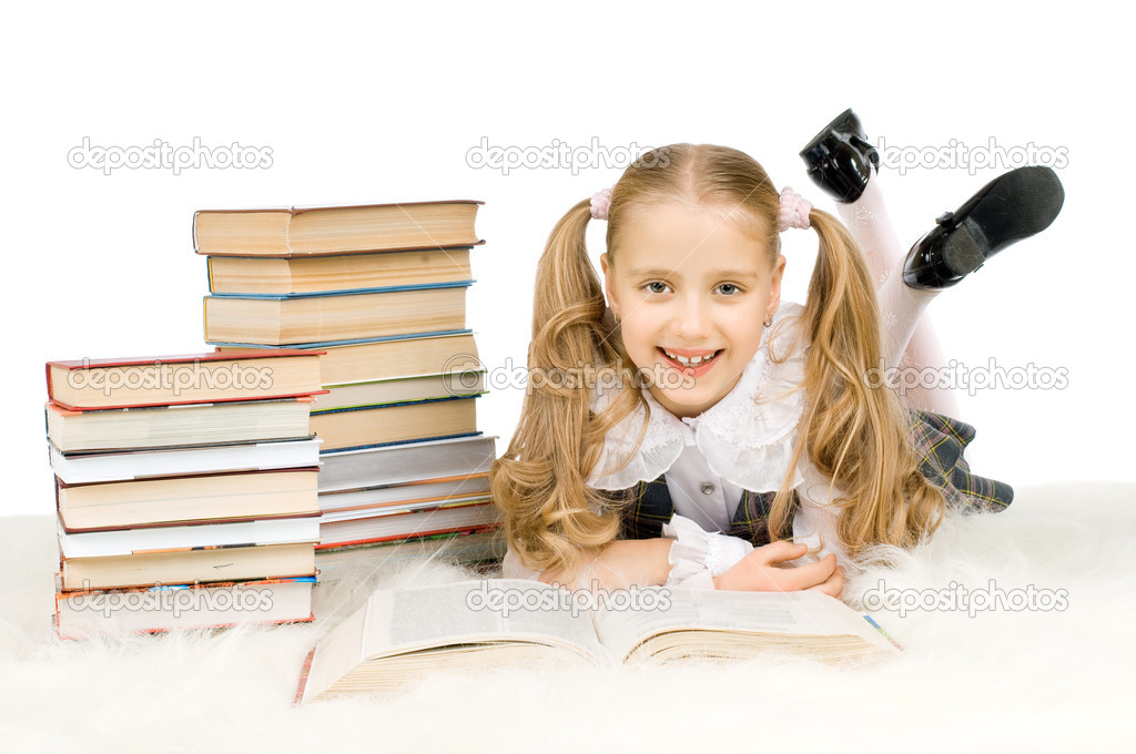 The cute little teen girl lie wih big textbook, smile, on white background, ...