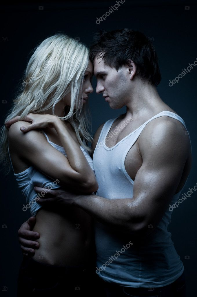 Muscular handsome sexy guy with pretty woman, on dark background, glamour blue light — Stock Photo #8220402
