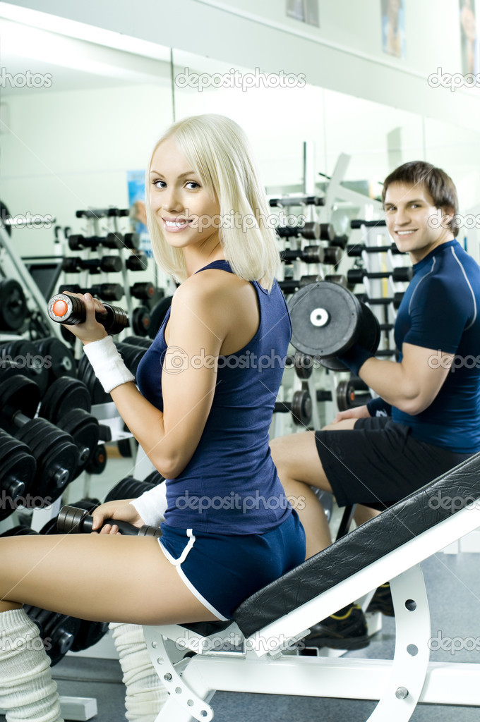 Happy cutie athletic girl and guy,  exercise with dumbbells and smile, in  sport-hall  Stock Photo #8220422