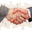 Shaking hands inside puzzle pieces — Stock Photo #10463289