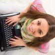 Happy female student with a laptop and notebooks — Stock Photo