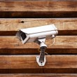 Camera on a wall of wooden houses - Stock Photo