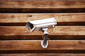 Camera on a wall of wooden houses — Stock Photo