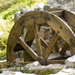 Old watermill with a wooden wheel and stone walls — Stock Photo