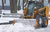 Tractor clears snow on city streets — Stock Photo