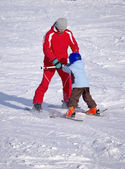 Instructor teaches a child to ride on skis — Stock Photo