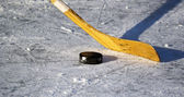Hockey stick and puck on the ice — Stock Photo