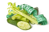 Diet concept. cucumbers and celery green with measure tape — Stock Photo