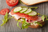 Sandwich with ham, tomato, cucumber and arugula on the old wooden cutting board — Stock Photo