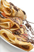 Pancakes with chocolate and strawberry syrup — Stock Photo