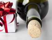 Bottle of red wine and a gift — Stock Photo