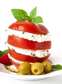 Tomato and mozzarella slices decorated with basil leaves on a plate and whi — Stock Photo