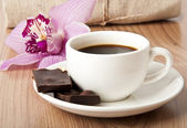 Cup of coffee, chocolate and orchid on wooden background — Stock Photo