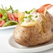 Baked potato filled with sour cream and arugula — Stock Photo #9835017