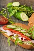 Kanapka z szynka, pomidor, ogórek i rukolą na stare drewniane krojenia — Zdjęcie stockowe