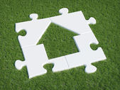 Puzzle house symbol on grass — Stock Photo