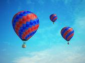 Três balões coloridos em um fundo de céu azul — Foto Stock