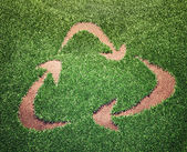 Recycling symbol in a field of grass — Photo