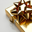 Gift box with a golden bow — Stock Photo