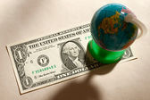 Terrestial globe and one dollar — Stock Photo
